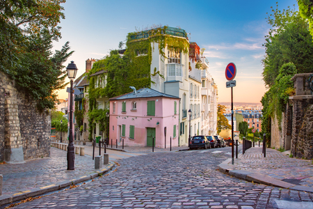 Foto de Cozy old street with pink house at the sunny sunrise, quarter Montmartre in Paris, France - Imagen libre de derechos