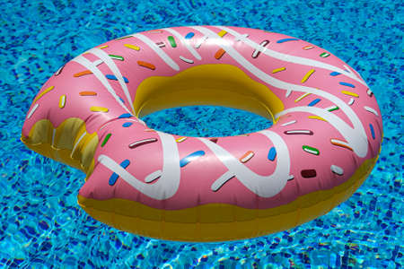 Photo pour pink inflatable donut doughnut floating mattress in swimming pool. Beach pool accessories. Summer holiday concept - image libre de droit