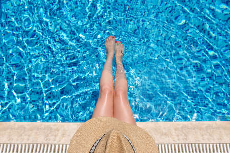 Photo pour Young woman in straw hat sunbathing sitting on the edge of swimming pool with legs in water. top view - image libre de droit