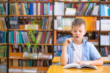 Photo pour A boy in a blue shirt in a library reads a book, thoughtfully nibbles a shackle of glasses while looking into a book - image libre de droit