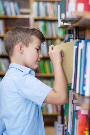 Photo pour A boy in a blue shirt in a library takes a book from a bookshelf - image libre de droit