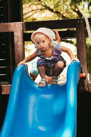 Happy little girl in hat playing on playground