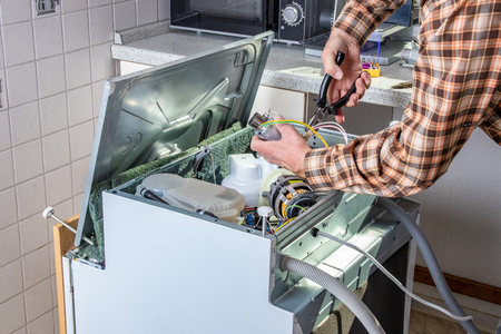 Photo pour People in technician jobs. Appliance repair technician or handyman works on broken dishwasher in a kittchen. Laborer is changing the heating element. - image libre de droit