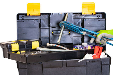 Photo for Plumber or carpenter tool box isolated. Black plastic tool kit box with assorted tools and a hand with glove holding a big screw with a big pipe wrench. Isolated on a white background. - Royalty Free Image