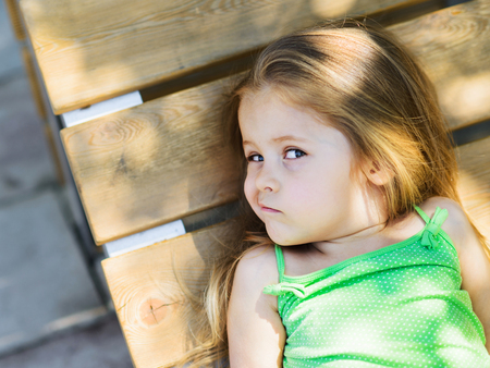 Foto de Cute little curly hair blonde girl lying on wooden bench looking at camera with scepticism - Imagen libre de derechos