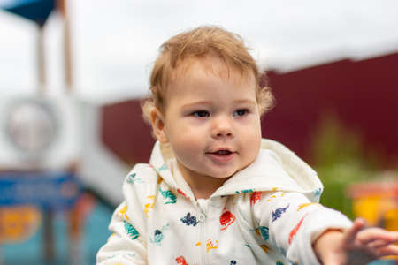 Photo pour Baby girl boy in a white jacket at the playground outdoor. Happy smiling Caucasian baby 1 year old on a walk, horizontal portrait. Curly hair kid - image libre de droit