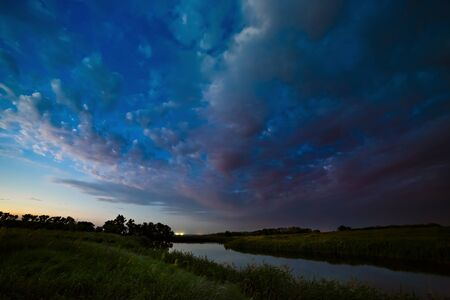Storm clouds in the sky after sunset on the river.