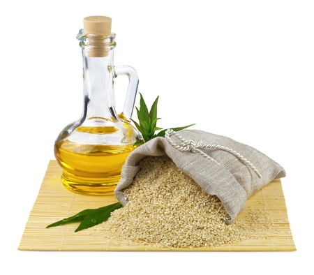 Macro view of sesame seeds in flax sack and glass bottle of sesame oil isolated on white background