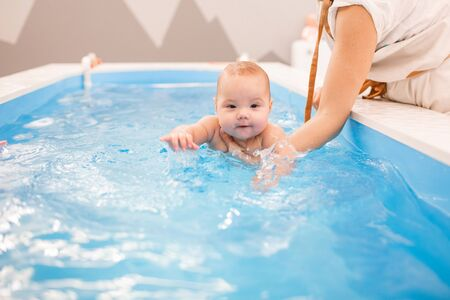 Photo pour Litle baby in pool swimming bathing during health procedures. Child swims in the hands of the instructor. - image libre de droit