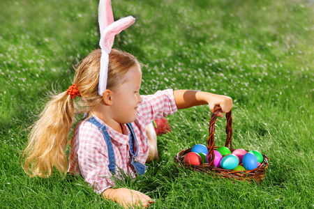 Photo for Cute little girl child with basket on green grass in the park. Easter Egg Hunting Concept - Royalty Free Image