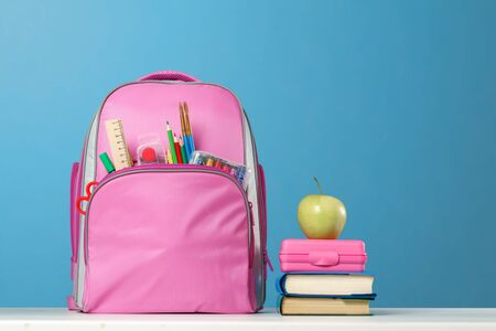 Photo for Student set. Pink backpack with stationery, a stack of books, a lunchbox, an apple on the table on a blue background. Back to school. - Royalty Free Image