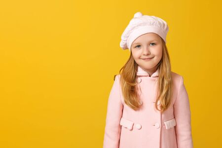 Foto de Portrait of a cheerful child in a pink coat and beret on a yellow background. Little girl blonde looks into the camera. Autumn concept. Copy space - Imagen libre de derechos