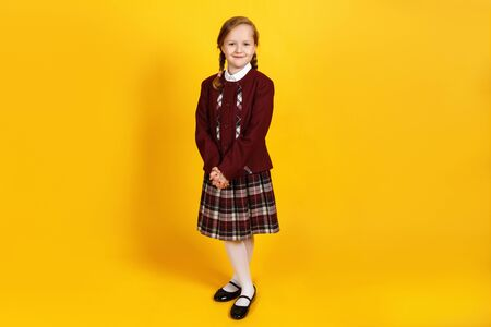 Photo for A full-length schoolgirl stands and looks at the camera. Cute little girl in uniform on a yellow background. - Royalty Free Image