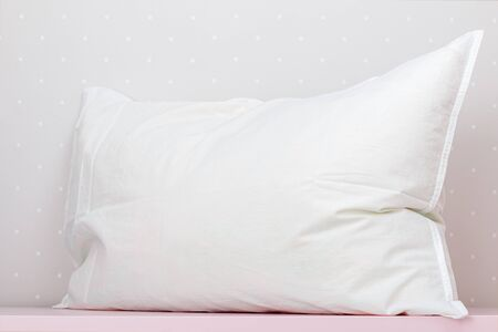 Photo pour Closeup of a white pillow on a table, against the background of a light wall. - image libre de droit