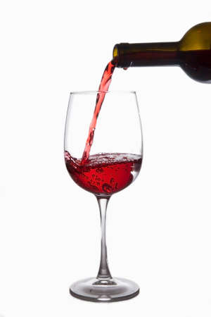 Photo pour Red wine is poured into a glass from a bottle, isolate on a white background - image libre de droit