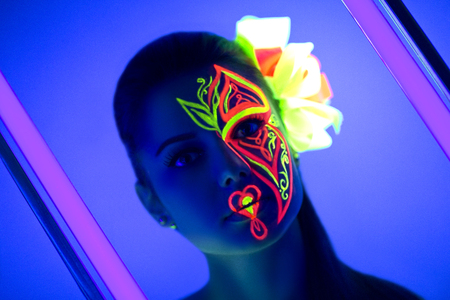Woman's face with fluorescent make up art.