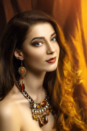Beautiful young woman, girl, lady, model, actress, wife, mistress. Stylish luxurious look. Expressive makeup, perfect eyebrows, eyes, lips. Color, golden, chocolate, caramel, brown. Chic hair, curls.