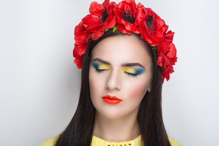 Closeup portrait of beautiful girl woman lady with volume combed hair styling. Luxury Bright makeup shiny lipstick cosmetics. New Professional photo model vip person, red flower accessory wreath poppy