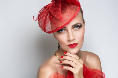 Closeup portrait of beautiful girl woman lady with bright make up. Luxury accessory tulle mesh makeup shiny lipstick cosmetics. Professional photo model vip person, red flower round hat diadem new art