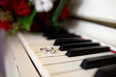 Big white black Piano keys and Two Wedding Rings. Flower bouquet composition of cream red yellow roses. Pleasant melody of unfading love, pure sublime feelings of two loving hearts. Concept conceptual