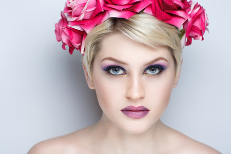 Closeup portrait of beautiful girl woman lady with short haircut hair styling. Luxury Bright makeup shiny lipstick cosmetics. New Professional photo model vip person, big flower accessory wreath roses