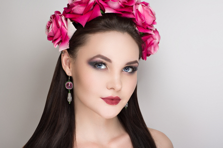 Closeup portrait of beautiful girl woman lady with volume combed hair styling. Luxury Bright makeup shiny lipstick cosmetics. New Professional photo model vip person, big flower accessory wreath roses