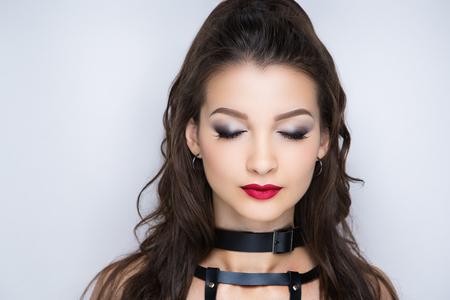 Beautiful woman, necklace choker leather belt. Professional cosmetics intensive makeup. Red matte lips lipstick lipgloss, shiny shadows. New photo close up portrait, gray color background horizontal