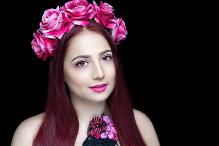 Photo pour Beautiful girl with a creative accessory on her head. A flower wreath adorns straight hair, large pink roses are a symbol of tenderness and femininity. White skin, bright summer makeup with pink lips - image libre de droit