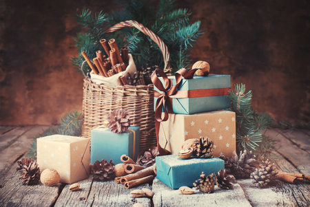 Festive Gifts with Boxes, Coniferous, Basket, Cinnamon, Pine Cones, Wallnuts on Wooden Background. Christmas Presents Toned in Vintage Style