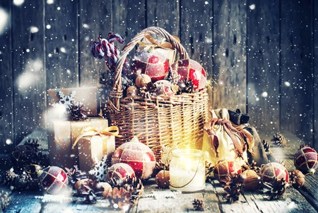 Christmas Gifts. Basket, Burning Candle, red balls, pine cones, snowflakes on Wooden Background. Vintage style with Drawn Snowfall