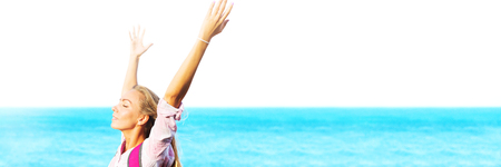 portrait young smiling happy long fare hair girl hands up having fun enjoying sun in front shore island sea morning. landscape open air view sunny day copy space