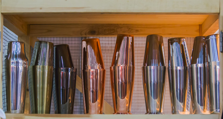 Gold and copper shakers, glasses and cookware for cocktails are at the bar.