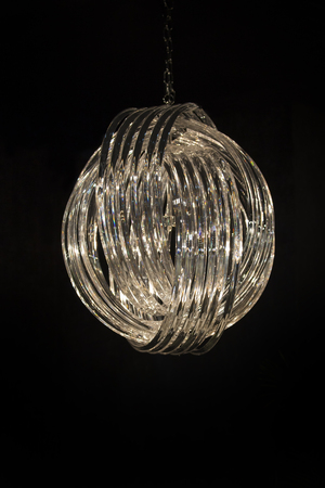 Foto de Fashionable designer chandelier in the form of rings decorated with glass crystals diamonds, chandelier isolate on a black background. - Imagen libre de derechos