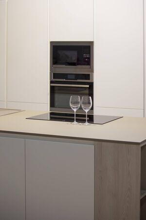 Photo pour Minimalistic kitchen design with island. Gray-white kitchen and wine glasses on the table. - image libre de droit