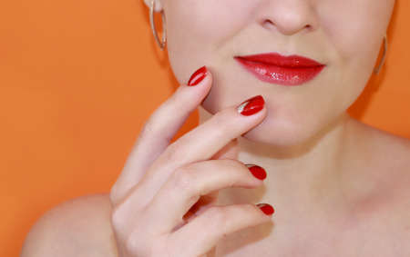 Photo pour Lips with red lipstick and red manicure on an orange background. Classic lipstick color. Byuti background. - image libre de droit
