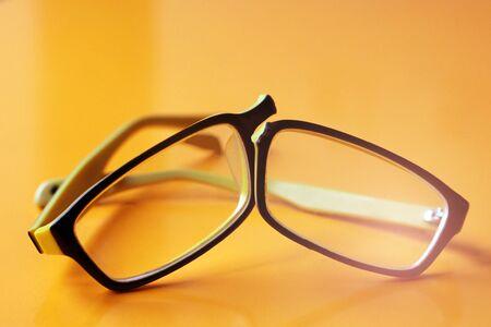 Photo pour Broken yellow glasses on orange background so close - image libre de droit