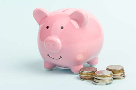 Photo pour Piggy bank with coin pile on blue background, space for text. Finance, saving money. Business to success and saving for retirement concept - image libre de droit