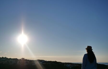 Photo pour A brunette girl with a hat standing against the sky is looking at the sunrise, copyspace - image libre de droit