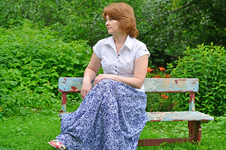 An adult woman sitting on a bench in the garden