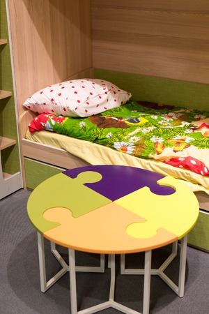 Fragment of interior children's room with a table in the form of a puzzle