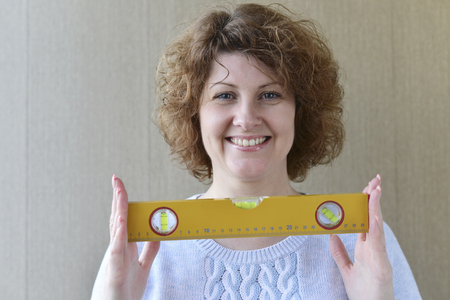 A woman is holding a construction tools