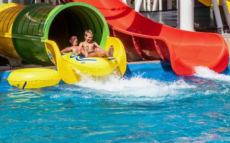 Photo pour Family is riding down the water park structure, sitting together at inflatable ring and surrounded by water splashes. Father and son, adult and teenager boy are enjoying weekend together at aquapark. - image libre de droit