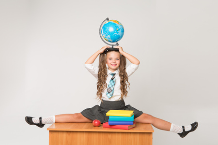 Happy little schoolgirl with globe on her head, wearing white blouse , standing against white background. Back to school concept. Ideal for banners, registration forms, presentation.