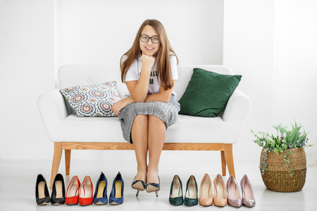 Foto de Young stylish girl and a lot of shoes. Concept fashion, shopping, clothing, lifestyle, shopping center. - Imagen libre de derechos