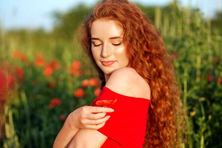 Beautiful young girl with very long red hair. Poppy field. Close-up. Beautiful make-up. The concept of health, nature, cosmetics and care.