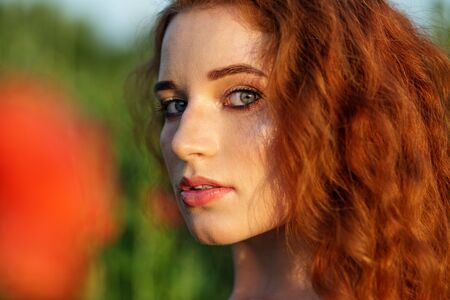 Beautiful girl with very long red hair. Poppy field. Close-up. Beautiful make-up. The concept of health, nature, cosmetics and care.