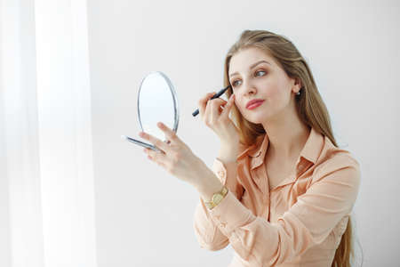 Photo pour A girl in a pastel-colored blouse is sitting at a makeup table, holding makeup brushes and making up, smiling mysteriously. - image libre de droit