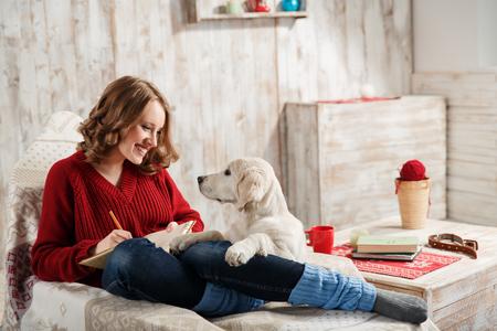 Foto de Young woman with her pet, golden retriever, relaxing together - Imagen libre de derechos