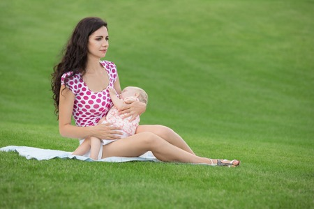 Photo for Young woman breastfeeding her baby outdoors at summer - Royalty Free Image
