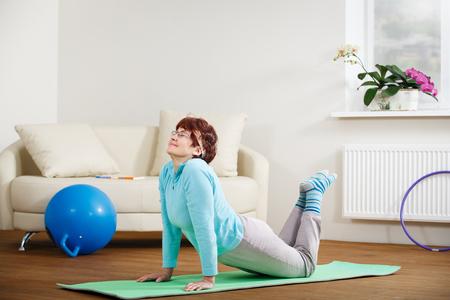 Photo pour Happy senior woman doing yoga at home - image libre de droit